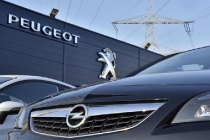An Opel car, in front, is offered for sale by a Peugeot dealer in Gelsenkirchen, Germany, Tuesday, Feb. 14, 2017. France's PSA Group, maker of Peugeot and Citroen cars, says it's exploring a takeover of Opel, General Motors' money-losing European business. (ANSA/AP Photo/Martin Meissner) [CopyrightNotice: Copyright 2017 The Associated Press. All rights reserved.]