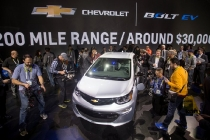Showgoers get a closer look at the 2017 Chevrolet Bolt EV during its world debut at the Consumer Electronics Show Wednesday, January 6, 2016 in Las Vegas, Nevada. The Bolt EV offers more than 200 miles of range on a full charge at a price below $30,000 after Federal tax credits. The Bolt EV also offers connectivity and infotainment technologies seamlessly integrating smartphones and other electronic devices. The Bolt EV will go into production by the end of 2016. (Photo by Isaac Brekken for Chevrolet)