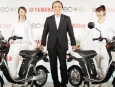 Yamaha Motor Co. President and Chief Executive Hiroyuki Yanagi, center, poses with his company's EC-03 electric scooters unveiled in Tokyo Wednesday, July 14, 2010. The 240,000 yen ($2,700)