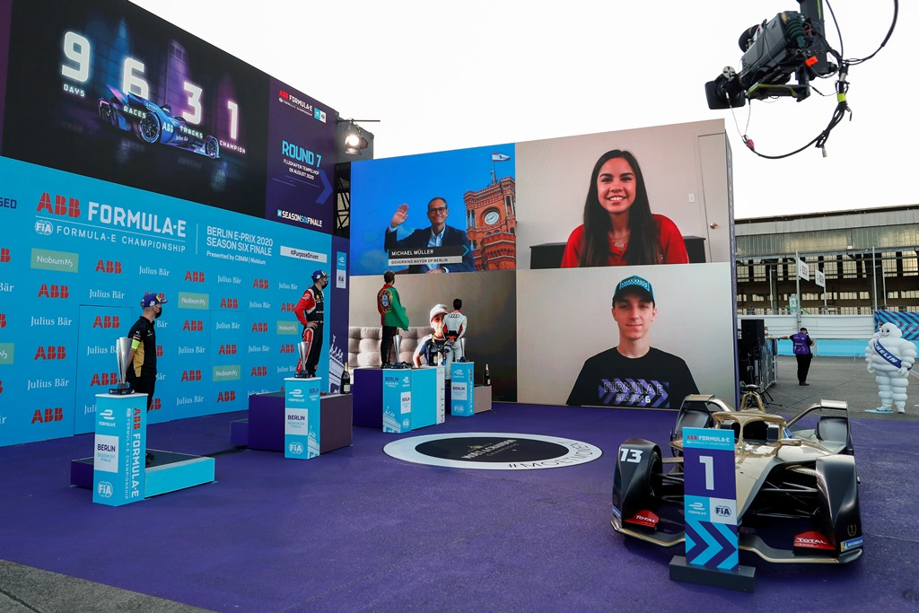 The trophy presenters on the big screen during the podium